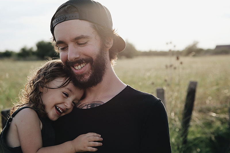outdoor late-day photo of father holding young daughter in field