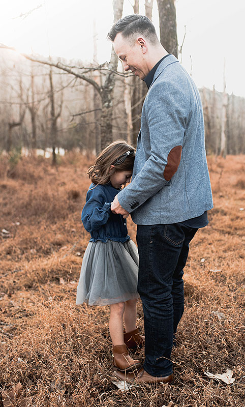 outdoor fall photo of father and young daughter who is standing on his feet