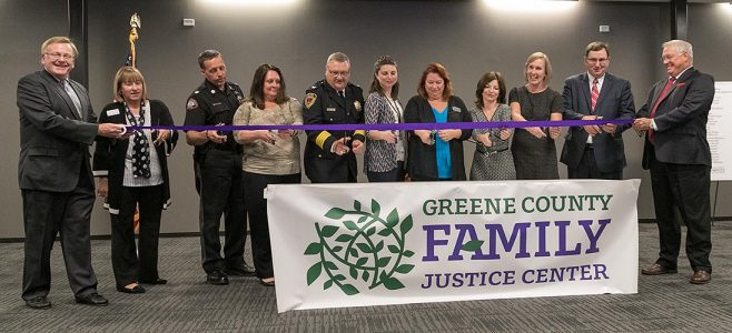 eleven people cutting a purple ribbon to celebrate a grand opening