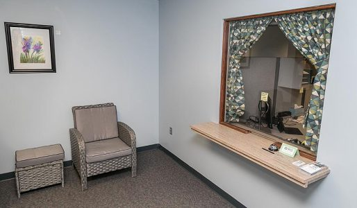 small light blue waiting room and receptionist window