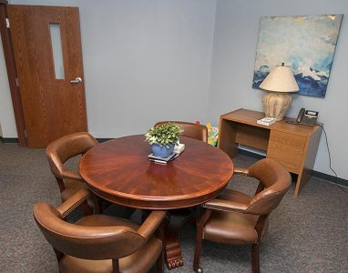 elegant round wood conference table that seats four people