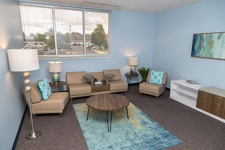light blue room with large window and retro modern furniture