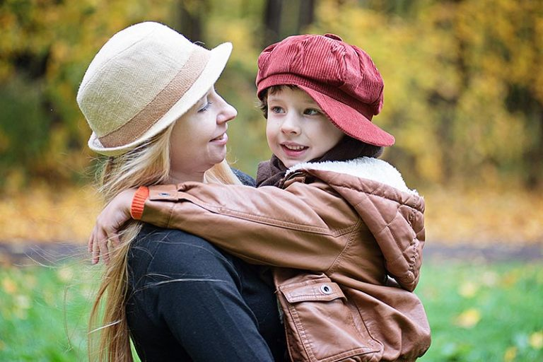 young mother holding young child outdoors in autumn