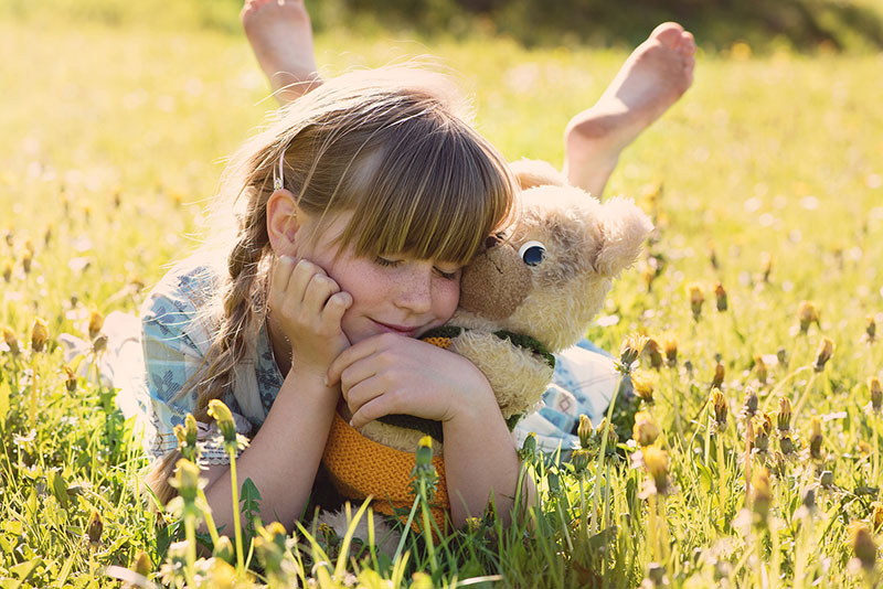 young girl laying in sunny field holding teddy bear